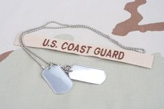 US COAST GUARD branch tape with dog tags on desert camouflage uniform Royalty Free Stock Photos