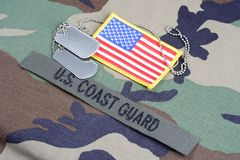 US COAST GUARD branch tape, flag patch and dog tags on woodland camouflage uniform Royalty Free Stock Images