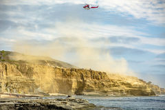 US coastguard helicopter in flight with clouds of dust royalty free stock image