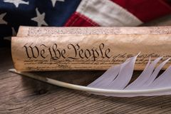 US Constitution on a Flag. United States Constitution, rolled in a scroll with quill on a vintage American flag and rustic wooden board Stock Image