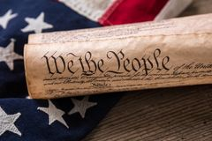 US Constitution on a Flag. United States Constitution, rolled in a scroll on a vintage American flag and rustic wooden board Royalty Free Stock Photo