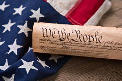 US Constitution on a Flag. United States Constitution, rolled in a scroll on a vintage American flag and rustic wooden board Stock Image
