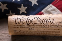 US Constitution on a Flag. United States Constitution, rolled in a scroll on a vintage American flag and rustic wooden board Stock Photos
