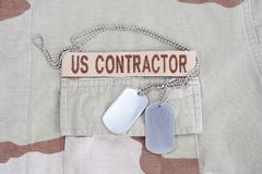 US CONTRACTOR branch tape with dog tags  and flag patch on desert camouflage uniform. US CONTRACTOR branch tape with dog tags patch on desert camouflage uniform Royalty Free Stock Image