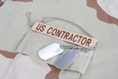 US CONTRACTOR branch tape with dog tags patch on desert camouflage uniform. Background Royalty Free Stock Photography