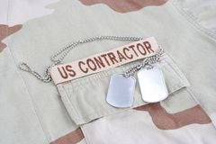 US CONTRACTOR branch tape with dog tags patch on desert camouflage uniform. Background Royalty Free Stock Photos