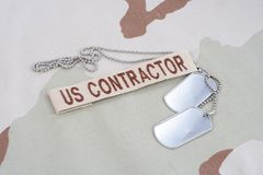 US CONTRACTOR branch tape with dog tags patch on desert camouflage uniform. Background Stock Photography