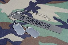 US CONTRACTOR branch tape and dog tags on woodland camouflage uniform. Background Royalty Free Stock Image