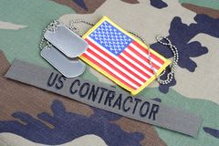 US CONTRACTOR branch tape, flag patch and dog tags on woodland camouflage uniform. Background Stock Photos
