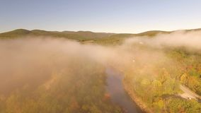 US Countryside Aerial. V4 Flying low over Deerfield River through thin morning fog at sunrise stock footage