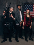 US criminal. Gangsters with weapon. Mixed nationality gang on american flag background. Outlaw, ghetto, social problem, robbery concept royalty free stock photo