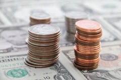 US Currency. Stacks of US coins on top of various dollar bills Stock Photos