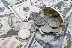 US  Dollar banknotes and coins. US  Dollar banknotes and coins, with focus on a quater dollar coin Stock Photo