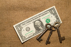 US dollar banknotes and keys on an old cloth Royalty Free Stock Photos