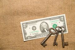 US dollar banknotes and keys on an old cloth Royalty Free Stock Images