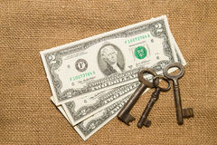 US dollar banknotes and vintage keys on an old cloth Stock Photos