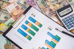 Us dollar bills and euro banknote and calculator on the graph. Concept of stock market trading - us dollar bills and euro banknote and calculator on the graph Stock Image