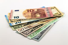 US dollar bills and Euro bills spread mixed on white background. Royalty Free Stock Images