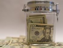 US Dollar bills in Glass Jar with other dollars around in soft focus Stock Images