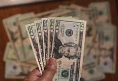 US Dollar bills in human hand with other dollars around in soft focus. US Dollar bills in hand with other dollars around in soft focus Royalty Free Stock Photos