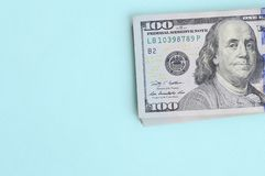 US dollar bills of a new design with a blue stripe in the middle is lies on a light blue background.  stock photos