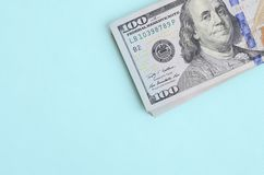US dollar bills of a new design with a blue stripe in the middle is lies on a light blue background.  royalty free stock photography