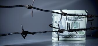 US Dollar bills wrapped in barbed wire as symbol of economic warfare, sanctions and embargo busting