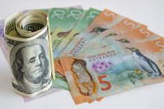 US Dollar currency notes on top of New Zealand currency bills Stock Images