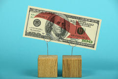 US dollar decline illustrated over blue. US crisis, decline of American dollar, one hundred US dollars banknote with red arrow down on wooden metal holders over stock photography