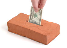 US Dollar deposit into a building brick. US Dollar bill in a piggy bank or tissue box like brick Stock Photos
