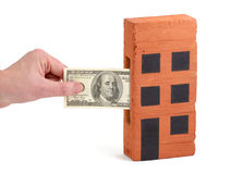 US Dollar deposit into a house-brick. US Dollar bill being inserted to or drawn from a block of flats Royalty Free Stock Photos