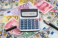 Us Dollar, Euro and Chinese Yuan banknote with calculator. On desk Stock Image