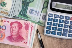 Us Dollar, Euro and Chinese Yuan banknote. With calculator on desk Royalty Free Stock Image