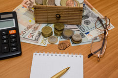 Us dollar and euro with empty notepad, glasses and calculator Stock Images