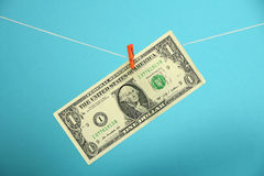 US dollar growth illustrated over blue. American economy growth, strengthening of US dollar illustrated, one dollar banknote hanged ascending with pin at rope Stock Photography