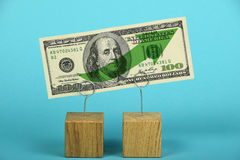 US dollar growth illustrated over blue. Growth and support of American economy and US dollar, one dollar banknote with green arrow up on two holders over blue Stock Image