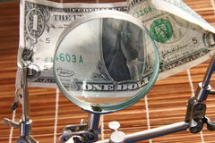 US dollar and magnifying glass. US dollar bill under a magnifying glass Royalty Free Stock Photography