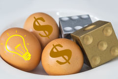 US Dollar sign and lamp on eggs with dices. Stock Images