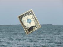 US dollar som sjunker i havet av globala marknader royaltyfri foto