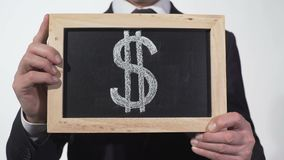 US dollar symbol on blackboard in businessman hands, world currency, finance. Stock footage stock video footage