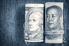 US dollar versus china yuan banknote on the wooden table background. The concept of business growth, financial or trade war.  royalty free stock photo