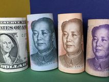 US dollar versus Chinese yuan. US dollar and Chinese yuan banknotes with blue, yellow and green background Stock Photos