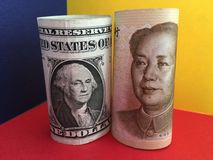 US dollar versus Chinese yuan. US dollar and Chinese yuan banknotes with blue, yellow and red background Stock Image
