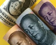 US dollar versus Chinese yuan. US dollar and Chinese yuan renminbi banknotes with yellow background Stock Image