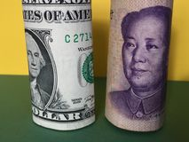 US dollar versus Chinese yuan. US dollar and Chinese yuan renminbi banknotes with yellow and green background Stock Images