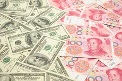 US dollar vs China yuan. Background of US one  hundred dollar bills vs China one hundred yuan bills