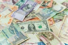 US dollarpengarräkning framme av andra internationella sedlar fotografering för bildbyråer