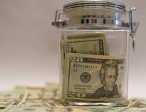 US dollarräkningar i den Glass kruset med andra dollar omkring i mjuk fokus Arkivbilder
