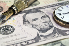 US Dollars. US Dollar bill with gold fountain pen and pocket watch. Differential focus