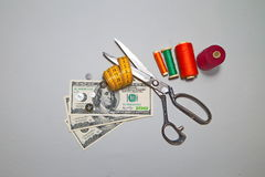 US Dollars and accessories for cutting and sewing. Can you make money sewing. US Dollars and accessories for cutting and sewing Stock Image